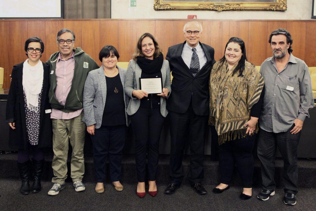 Daniella Meggiolaro, diretora do IDDD responsável pelo projeto, recebe a placa de menção honrosa entregue pelo vereador Eduardo Suplicy, que presidiu a sessão solene da premiação